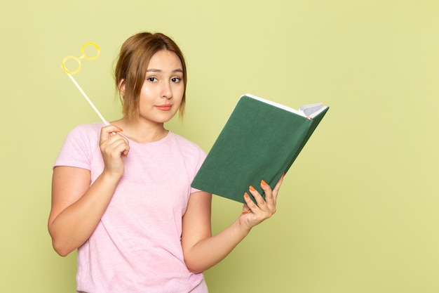 Widok Z Przodu Młoda Piękna Dziewczyna W Niebieskich Dżinsach Różowy T-shirt Pozowanie Z Zabawkowymi Okularami Przeciwsłonecznymi, Czytając Książkę Na Zielono Darmowe Zdjęcia