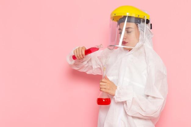 Widok Z Przodu Młoda Piękna Kobieta W Specjalnym Białym Garniturze, Ubrana W Kask Ochronny, Mieszająca Rozwiązania Na Różowej Kobiecie Skafander Kosmiczny Darmowe Zdjęcia