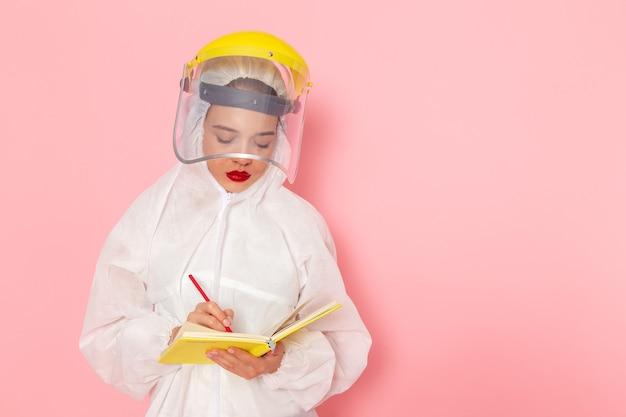 Widok Z Przodu Młoda Piękna Kobieta W Specjalnym Białym Garniturze Ubrana W Kask Ochronny Zapisująca Notatki Na Temat Różowej Kobiety Skafandra Darmowe Zdjęcia