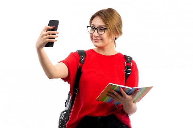 Widok Z Przodu Młoda Studentka W Czerwonej Koszulce Na Sobie Czarną Torbę Trzymając Zeszyt I Czarny Smartfon, Biorąc Selfie Biały Darmowe Zdjęcia
