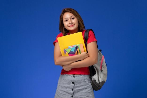 Widok Z Przodu Młoda Studentka W Czerwonej Koszuli Na Sobie Plecak, Trzymając Zeszyt I Pliki Na Jasnoniebieskim Tle. Darmowe Zdjęcia