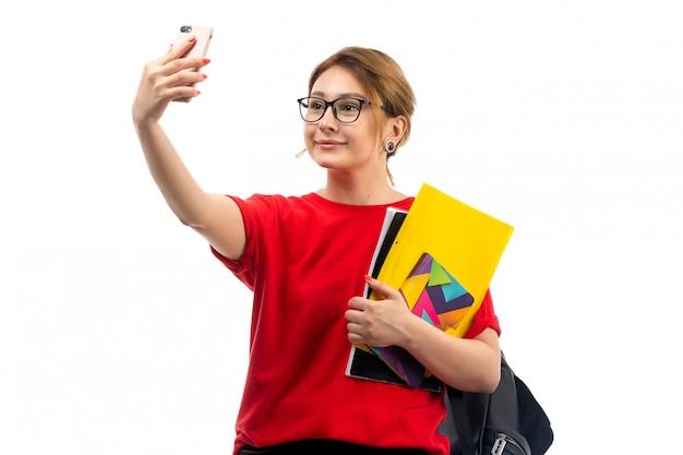 Widok Z Przodu Młoda Studentka W Czerwony T-shirt Czarne Dżinsy, Trzymając Zeszyty, Biorąc Selfie Na Białym Darmowe Zdjęcia
