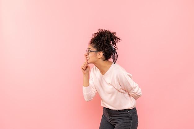Widok Z Przodu Młodej Kobiety Proszącej O Milczenie Na Różowej ścianie Darmowe Zdjęcia