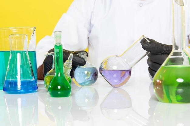 Widok Z Przodu Młody Chemik Mężczyzna W Białym Garniturze Przed Stołem Z Kolorowymi Roztworami Pracującymi Z Nimi Na żółtej ścianie Laboratorium Naukowe Chemia Darmowe Zdjęcia