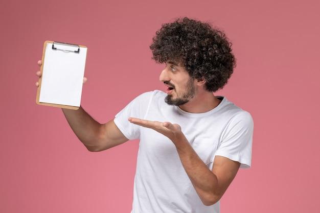 Widok Z Przodu Młody Człowiek Zaskakujący Jego Biały Notatnik Na Różowym Tle Darmowe Zdjęcia