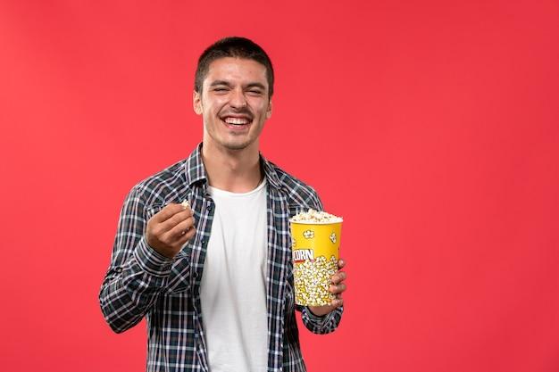 Widok Z Przodu Młody Mężczyzna Trzymający Popcorn I śmiejący Się Na Jasnoczerwonej ścianie Męskie Filmy Teatralne Kino Darmowe Zdjęcia