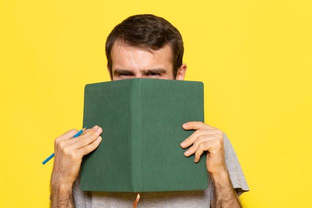 Widok Z Przodu Młody Mężczyzna W Szarej Koszulce, Trzymając Zielony Zeszyt Na żółtej ścianie Mężczyzna Kolor Ubrania Modelu Emocji Darmowe Zdjęcia