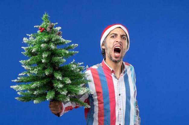 Widok Z Przodu Młody Mężczyzna Zły Na Drzewo Nowego Roku Na Niebieskiej ścianie Wakacje Emocji Nowego Roku Darmowe Zdjęcia