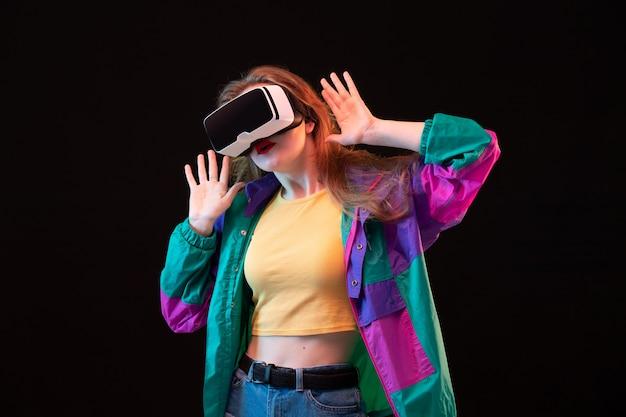 Widok Z Przodu Nowoczesna Młoda Dama W Kolorowym Pomarańczowym Płaszczu, Grająca I Próbująca Vr Na Czarnym Tle Interaktywna Gra Darmowe Zdjęcia