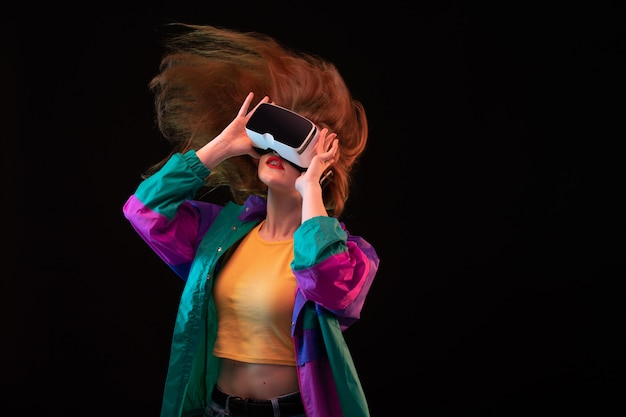 Widok Z Przodu Nowoczesnej Młodej Damy W Pomarańczowej Koszulce W Kolorowym Płaszczu, Grającej W Wirtualną Rzeczywistość Na Czarnym Tle Interaktywnej Gry Darmowe Zdjęcia