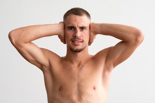 Widok Z Przodu Półnagi Mężczyzna Pokazujący Bicepsy, Zakrywając Uszy Darmowe Zdjęcia