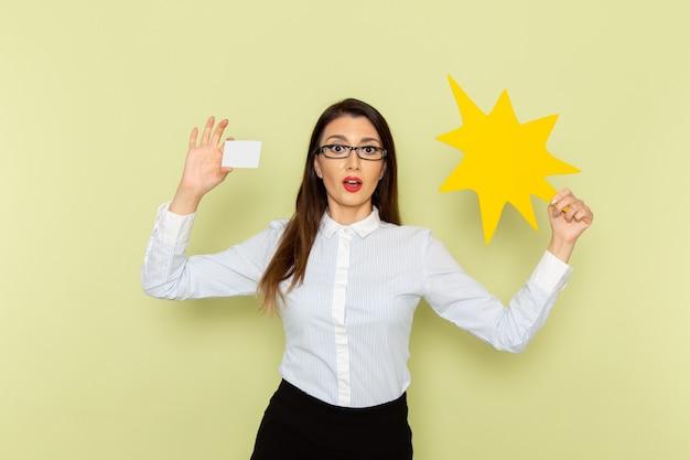Widok Z Przodu Pracownica Biurowa W Białej Koszuli I Czarnej Spódnicy, Trzymając Białą Kartę I żółty Znak Na Zielonej ścianie Darmowe Zdjęcia