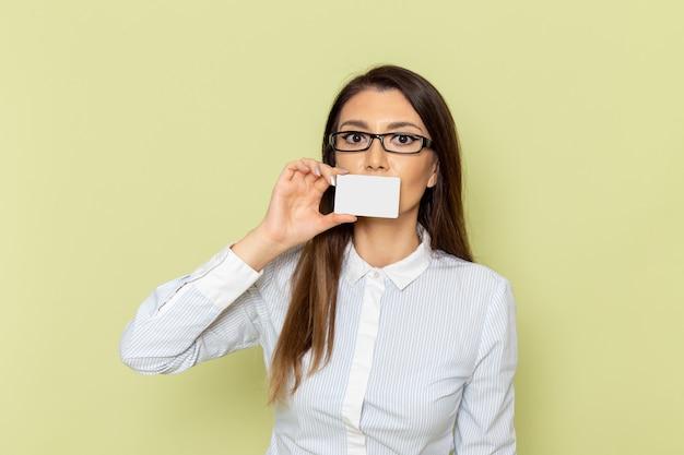 Widok Z Przodu Pracownica Biurowa W Białej Koszuli I Czarnej Spódnicy, Trzymając Białą Plastikową Kartę Na Zielonej ścianie Darmowe Zdjęcia