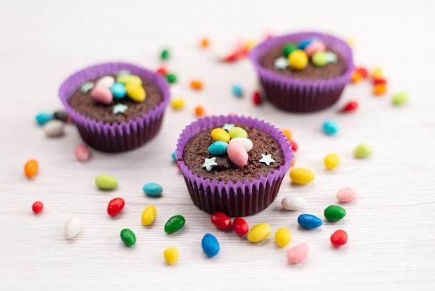 Widok Z Przodu Pyszne Ciasteczka W Fioletowych Formach Z Kolorowymi Cukierkami Na Białych, Cukierkowych Cukierkach Darmowe Zdjęcia
