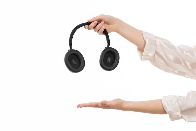 Widok Z Przodu Ręka Trzyma Czarne Słuchawki Pokazujące Pustą Dłoń Na Białym Darmowe Zdjęcia