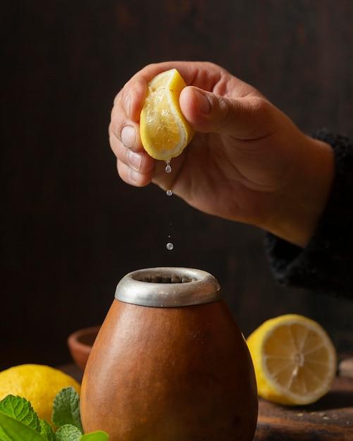 Widok Z Przodu Ręka Wyciskająca Cytrynę Nad Herbatą Darmowe Zdjęcia