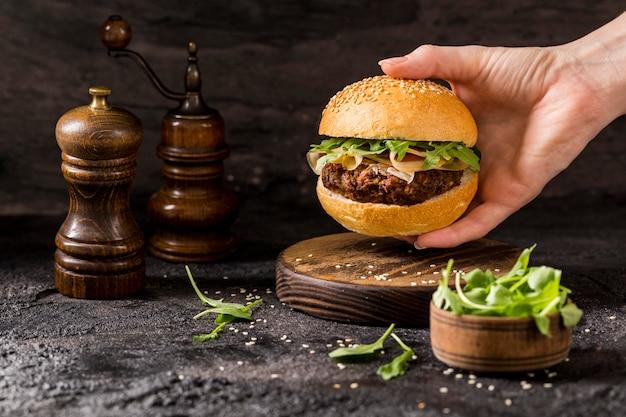 Widok Z Przodu Ręki Trzymającej Burgera Wołowego Z Sałatką I Boczkiem Darmowe Zdjęcia