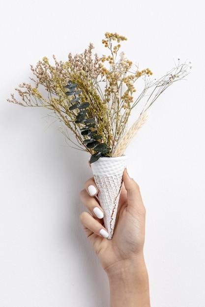 Widok Z Przodu Ręki Trzymającej Stożek Lody Z Kwiatami Darmowe Zdjęcia