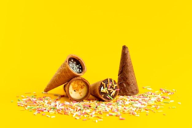 Widok Z Przodu Rogów Lodów Wraz Z Wielobarwnymi Drobinkami Cukierków Na żółtym, Kandyzowanym Kolorze Słodkiego Cukru Darmowe Zdjęcia