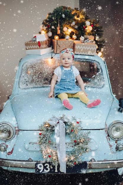Widok Z Przodu Słodkie I Modne Małe Słodkie Dziewczyny Siedzącej Na Niebieski Samochód Retro Ozdobione Na Boże Narodzenie. Premium Zdjęcia