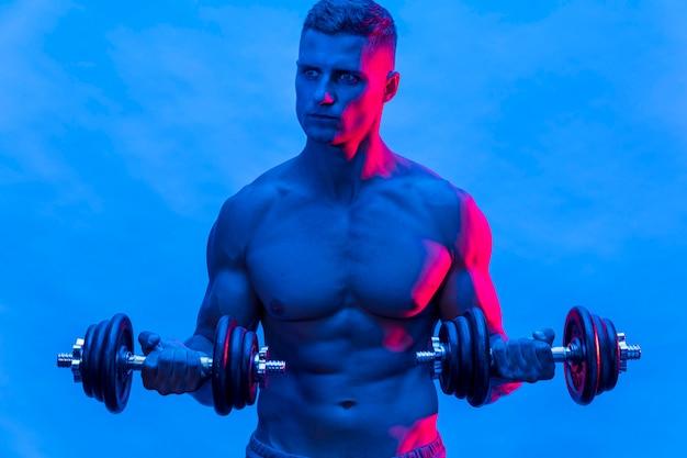 Widok Z Przodu Sprawnego Mężczyzny Bez Koszuli Trenującego Z Ciężarami Darmowe Zdjęcia