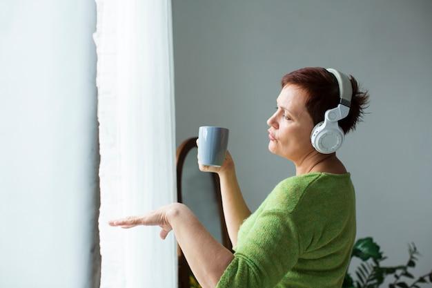 Widok z przodu starsza kobieta tańczy i słucha muzyki Darmowe Zdjęcia