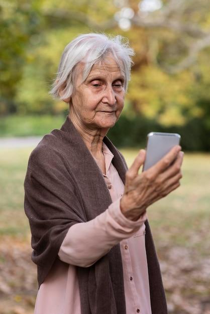 Widok Z Przodu Starszej Kobiety Trzymającej Smartfon Darmowe Zdjęcia