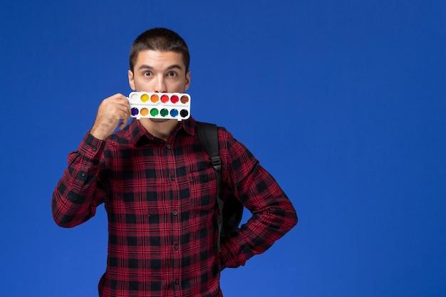 Widok Z Przodu Studenta W Czerwonej Koszuli W Kratkę Z Plecakiem Trzymającym Farby Do Rysowania Na Niebieskiej ścianie Darmowe Zdjęcia