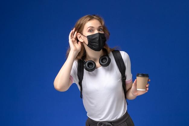 Widok Z Przodu Studentki W Białej Koszuli Na Sobie Czarną Maskę Plecaka I Trzymając Kawę, Próbując Usłyszeć Na Niebieskiej ścianie Darmowe Zdjęcia