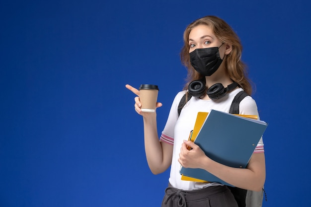 Widok Z Przodu Studentki W Białej Koszuli Na Sobie Czarną Maskę Plecaka, Trzymając Kawę I Pliki Na Niebieskim Biurku Darmowe Zdjęcia
