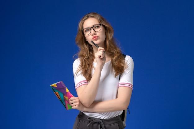 Widok Z Przodu Studentki W Białej Koszuli Trzymając Pióro I Zeszyt Myśli Na Niebieskiej ścianie Darmowe Zdjęcia