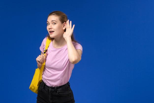 Widok Z Przodu Studentki W Różowej Koszulce Z żółtym Plecakiem Próbującej Usłyszeć Na Niebieskiej ścianie Darmowe Zdjęcia