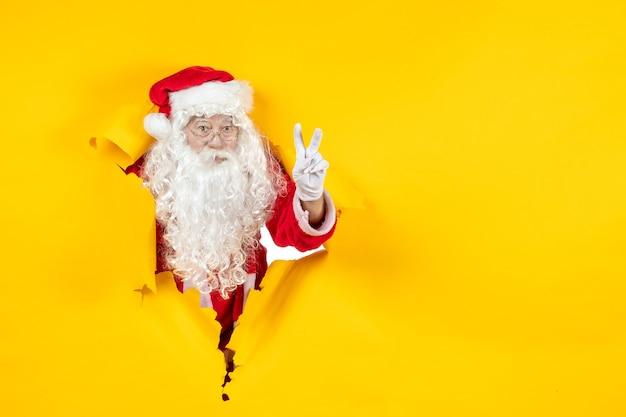 Widok Z Przodu świętego Mikołaja Patrząc Przez żółtą ścianę Zgrywanie Papieru Darmowe Zdjęcia