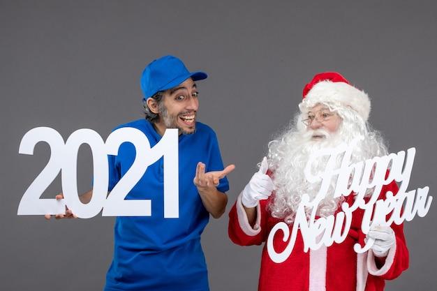 Widok Z Przodu świętego Mikołaja Z Męskim Kurierem Trzymającym Szczęśliwego Nowego Roku I Tablice 2021 Na Szarej ścianie Darmowe Zdjęcia