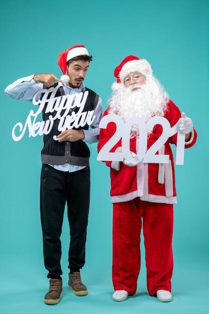 Widok Z Przodu świętego Mikołaja Z Mężczyzną Trzymającym Tablice Szczęśliwego Nowego Roku 2021 Na Niebieskiej ścianie Darmowe Zdjęcia