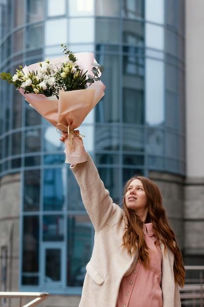 Widok Z Przodu Szczęśliwa Kobieta Trzyma Bukiet Kwiatów Na Zewnątrz Premium Zdjęcia