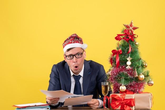 Widok Z Przodu Szczęśliwy Człowiek Biznesu Sprawdzanie Dokumentów Siedzi Przy Stole W Pobliżu Choinki I Przedstawia Na żółto Darmowe Zdjęcia