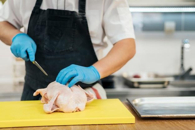 Widok Z Przodu Szefa Kuchni W Rękawiczkach Do Cięcia Kurczaka Darmowe Zdjęcia