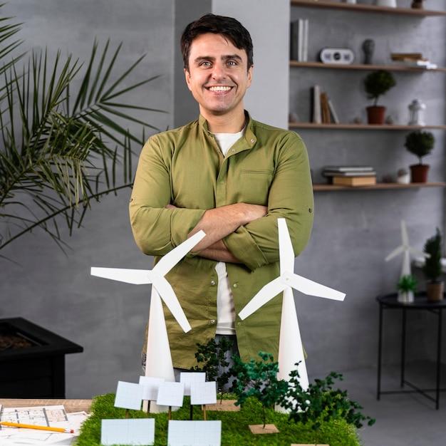 Widok Z Przodu Uśmiechniętego Człowieka Pracującego Nad Ekologicznym Projektem Energii Wiatrowej Z Turbinami Wiatrowymi Darmowe Zdjęcia
