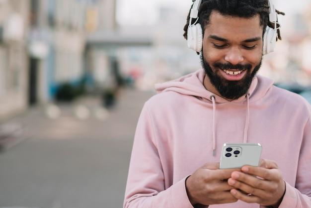 Widok Z Przodu Uśmiechniętego Człowieka Za Pomocą Smartfona Ze Słuchawkami Na Zewnątrz Premium Zdjęcia