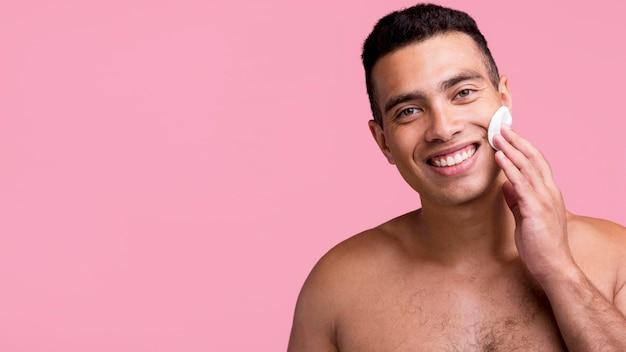 Widok Z Przodu Uśmiechniętego Mężczyznę Bez Koszuli Za Pomocą Wacików Na Twarzy Darmowe Zdjęcia