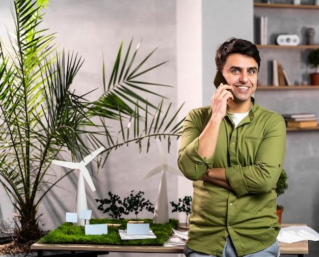 Widok Z Przodu Uśmiechniętego Mężczyzny Rozmawiającego Przez Telefon Obok Ekologicznego Układu Projektu Energii Wiatrowej Darmowe Zdjęcia