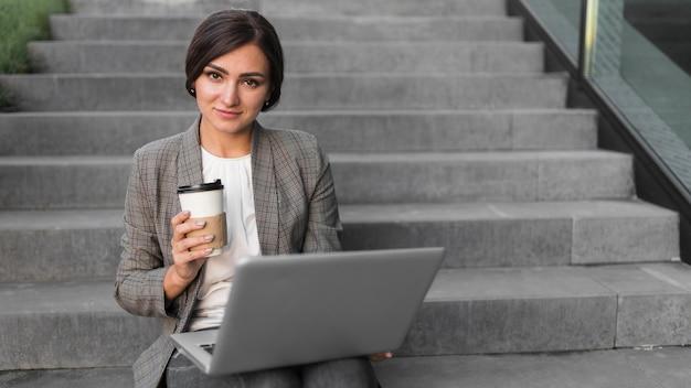 Widok Z Przodu Uśmiechniętej Bizneswoman Pracuje Na Laptopie Na Schodach Darmowe Zdjęcia