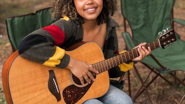 Widok Z Przodu Uśmiechniętej Kobiety Grającej Na Gitarze Podczas Kempingu Na świeżym Powietrzu Darmowe Zdjęcia