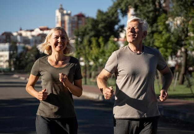 Widok Z Przodu Uśmiechniętej Starszej Pary Jogging Na Zewnątrz Premium Zdjęcia
