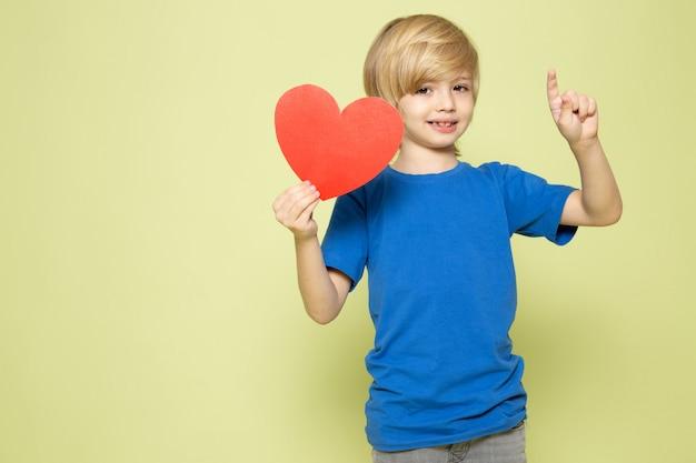Widok Z Przodu Uśmiechnięty Blond Chłopiec Trzyma Kształt Serca W Niebieskiej Koszulce Na Kamiennej Przestrzeni Darmowe Zdjęcia