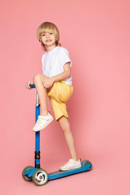 Widok Z Przodu Uśmiechnięty Chłopiec Blondynka W Białej Koszulce Jazda Skuterem Na Różowej Przestrzeni Darmowe Zdjęcia