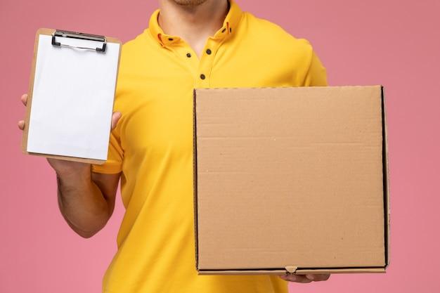 Widok Z Przodu Z Bliska Mężczyzna Kurier W żółtym Mundurze, Trzymając Notatnik I Pudełko Dostawy żywności Na Różowym Tle Darmowe Zdjęcia