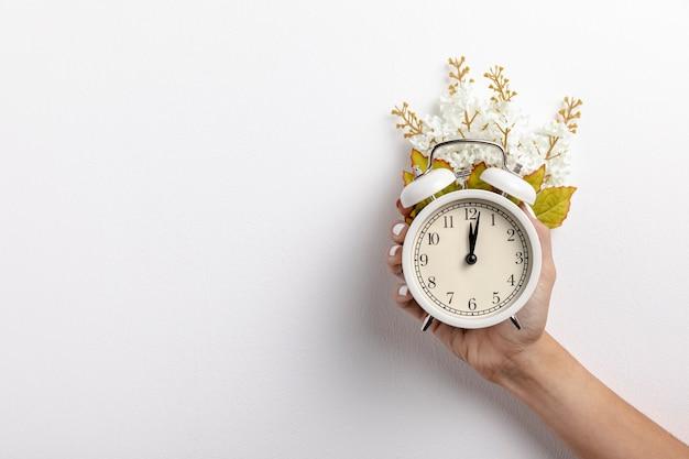Widok Z Przodu Zegara Trzymanego W Ręku Z Liści I Kwiatów Darmowe Zdjęcia