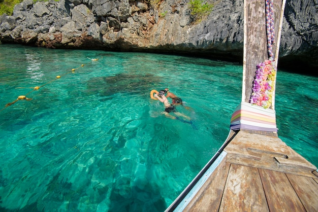 Widok Z Tradycyjnej Tajskiej łodzi Longtail, Podczas Gdy Turyści Snorkeling I Nurkowanie W Oceanie, Wyspy Phi Phi, Tajlandia Premium Zdjęcia